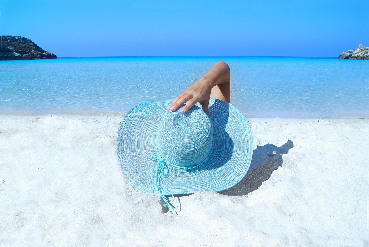 Femme allongé sur une plage, portant un grand chapeau pour se protéger du soleil